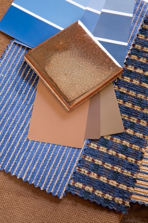 Blue and brown paint color and fabric swatches with a ceramic floor tile