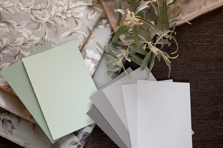 Light green and neutral gray paint color and fabric swatches  with a tile. photo