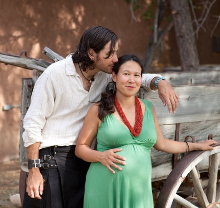 Happy young couple expecting a baby, posing by an old wagon. Banco de Imagens