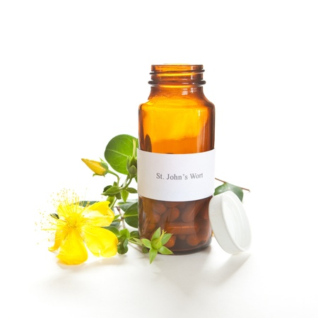 St. Johns Wort capsules with a Hypericum perforatum plant on white. The label was made for the photo shoot, no copyright or brand name infringement issues. photo