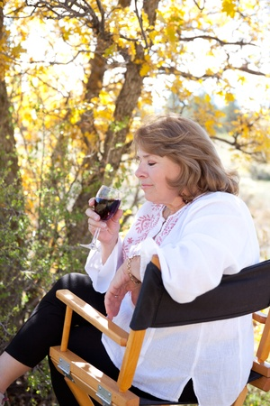 sniff: Woman enjoying her red wine, taking the first sniff. Stock Photo