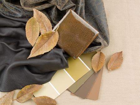 Aards bruinachtig interieur plan - handgemaakte keramische tegel met twee bruine lederen monsters en verf kleurstalen. Stockfoto