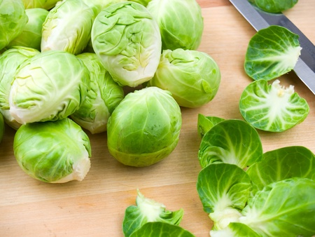 cruciferous: Fresh brussel sprouts on a wooden cutting board Stock Photo