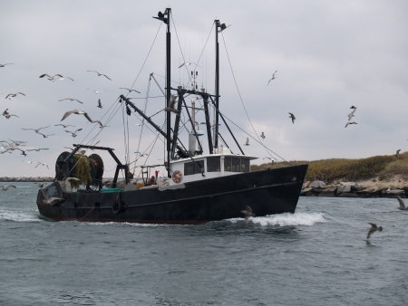 Commercial fishing boat returning to harbor Stock Photo