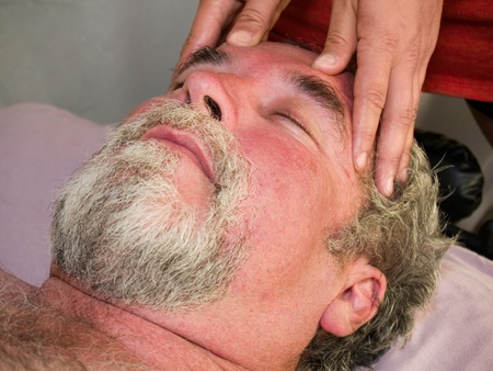 reiki: Man in his 50s getting a head massage