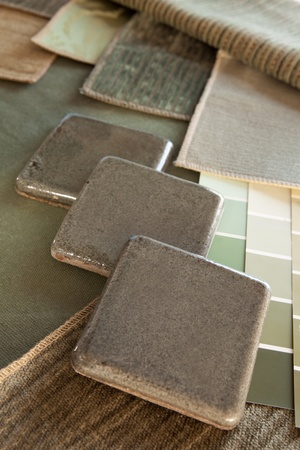 Earthy green brown interior design plan with fabric and paint color swatches, and ceramic tiles.