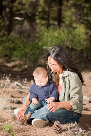 Native American mother and her mixed race baby boy enjoying a day in the nature. Shallow DOF, focus on womans face.