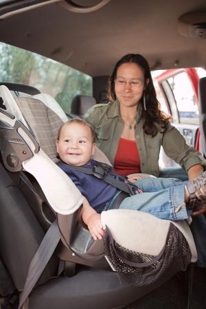 Reizen met een baby. Moeder en baby in de achterbank van een auto op een road trip.