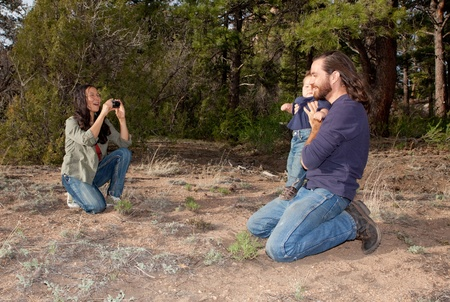 Mother taking a picture of father and son outdoors in nature photo