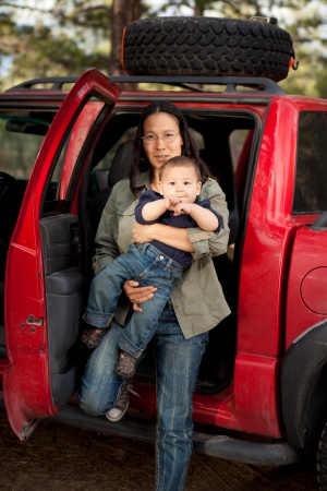 native american indian: Mother stepping out of the back seat of a car with a baby  Shallow DOF, boy
