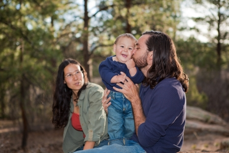 mixed family: Father kissing baby boy, mother sitting in the background  Shallow DOF, focus on baby  Stock Photo