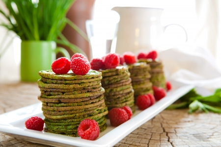 nettle: Traditional Scandinavian nettle or spinach pancakes with raspberries Stock Photo