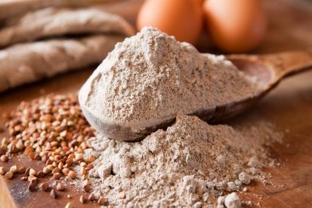 Buckwheat flour in a wooden measuring spoon