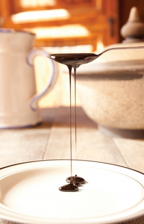 Blackstrap molasses drizzling from a teaspoon