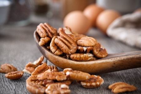 whole pecans: Pecans in a wooden spoon