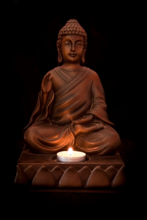 buddah: Buddha statue with a candle on a black background Stock Photo