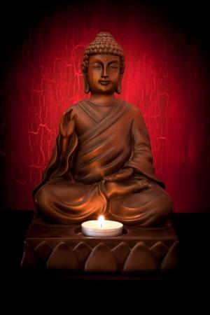 Boeddhabeeld met een kaars op een rode achtergrond