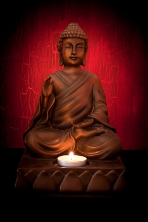 Buddha statue with a candle on a red background
