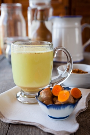 Golden milk  Turmeric herbal medicine, an anti-inflammatory  Shallow DOF, focus on the brim of the glass and the foam on milk