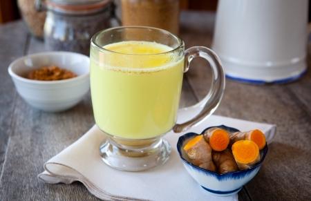 Golden melk Kurkuma kruidengeneeskunde, een anti-inflammatoire Ondiepe DOF, focus op de rand van het glas en het schuim op de melk