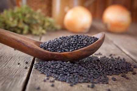 lentejas: Lentejas negras en una cuchara de madera