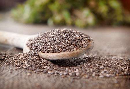 Black chia seeds on a wooden spoon Stockfoto