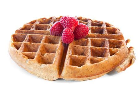 Homemade whole grain waffle with raspberries on white
