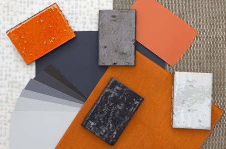 Orange and gray interior fabric and tile samples and paint swatches