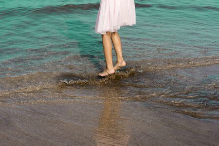 A happy girl child having fun in the beach splashing in the water. Unrecognizable human child.