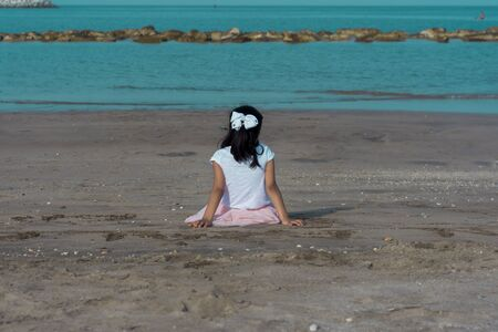A lonely child daydreaming in the beach side. Unrecognizable human child. Standard-Bild