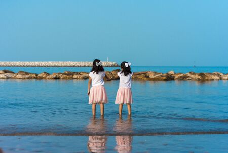 Two happy sibling sisters having super fun-time in the sea water in summer. Unrecognizable human child. Stok Fotoğraf - 131958039