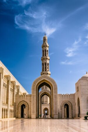 Muscat,Oman-22nd july 2019. Sultan Quaboos Grand Mosque minaret with beautiful clouds and blue sky, Islamic traditional religious architecture and landscape.