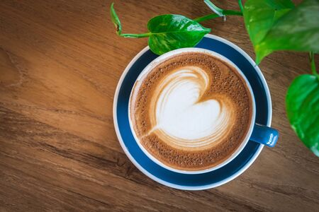 Beautiful a blue cup of hot cappuccino coffee with latte art on wooden coffee table, selective focus for drink background Reklamní fotografie