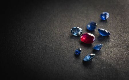 Collection of red ruby and blue sapphire, Precious stones for jewellery on black matte paper background, rough paper