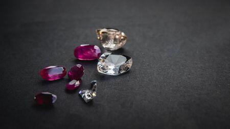 Collezione di rubini rossi e topazio, pietre preziose per gioielli su sfondo di carta nera opaca, carta ruvida Archivio Fotografico