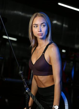 beautiful blond doing weight training in Gym with weights and machine Imagens