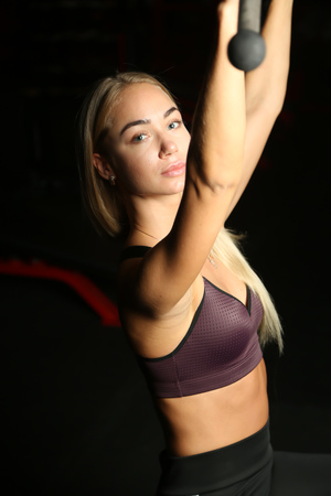 beautiful blond doing weight training in Gym with weights and machine Stock Photo