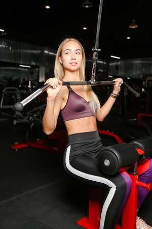 beautiful blond doing weight training in Gym with weights and machine 免版税图像
