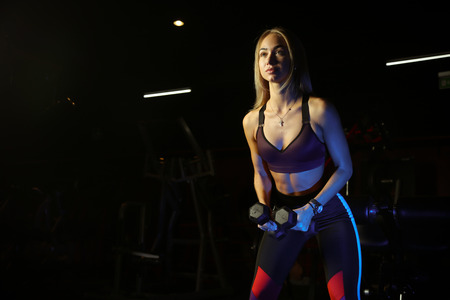 beautiful blond doing weight training in Gym with weights and machine Banque d'images