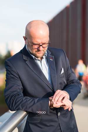 expected: The photo shows a man looking at his watch, which is expected to meet. Stock Photo