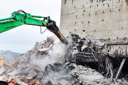 Excavator working at the demolition of an old industrial building. 版權商用圖片
