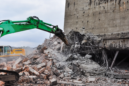 Excavator working at the demolition of an old industrial building. Stock Photo