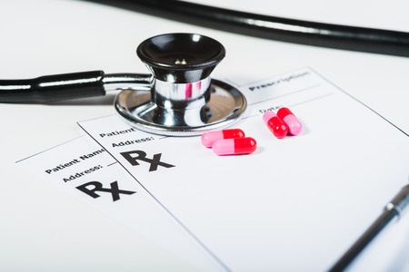 Prescription drugs overvoltage by a doctor. Antibiotics, pills, stethoscope. Make out a prescription for something.  Stock Photo