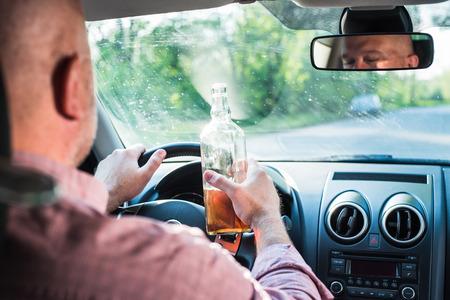 Im Bild zu trinken ein Mann Alkohol im Auto.