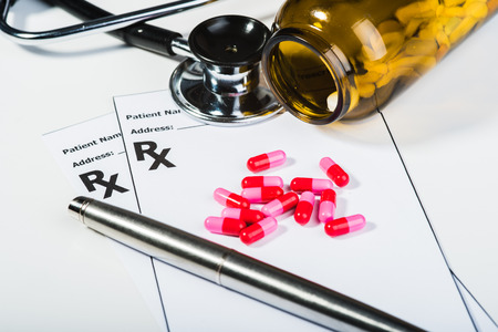 myocardial: Prescription drugs overvoltage by a doctor. Antibiotics, pills, stethoscope. Make out a prescription for something.