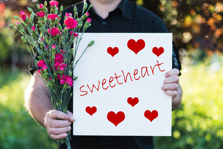 Man holding flowers and board - sweetheart Stock Photo