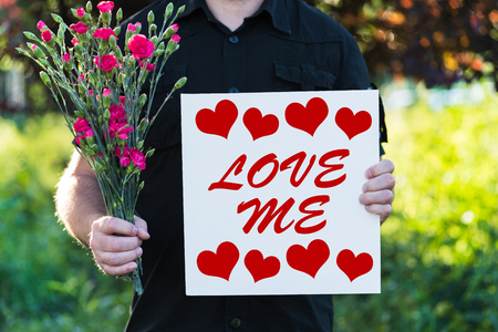 Man holding flowers and board - love me Stock Photo