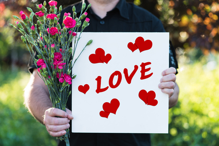 Man holding flowers and board - love