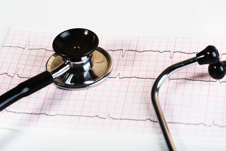 Examination of electrocardiography and a stethoscope on a white background. The questionnaire patient history.Medical materials.