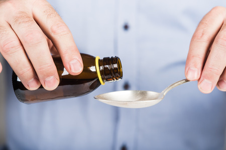 Taking cough syrup. Medicine liquid served on a spoon.